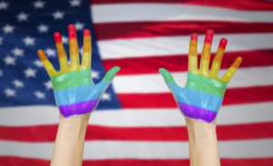 hands painted in rainbow colours and american flag